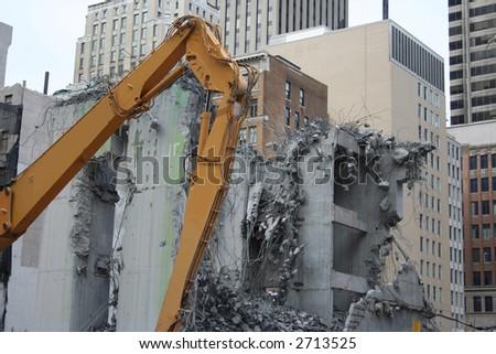 skyscraper demolition with heavy machinery and rubble - stock photo