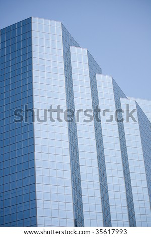 Skyscraper Glass Window Panel Office Building set against a blue sky background.