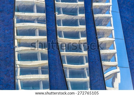 Skyscraper in construction reflected in the mirrors of a lilac wall - stock photo