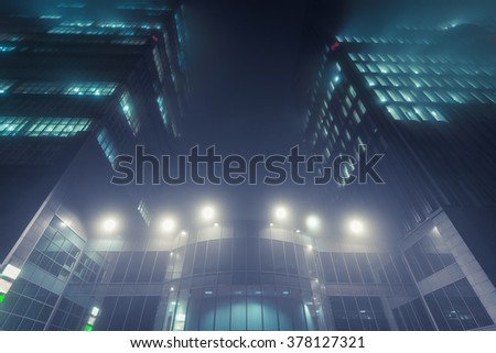 Skyscraper in fog with glowing windows at night - stock photo