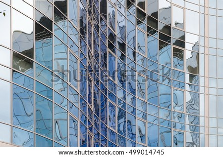 Skyscraper mirror glass surface reflecting cloudy sky, curvy surface