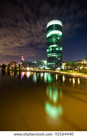 Skyscraper office on the river at night in Frankfurt - stock photo