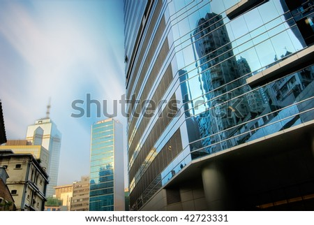 Skyscraper stands on the street with blue sky and white clouds.