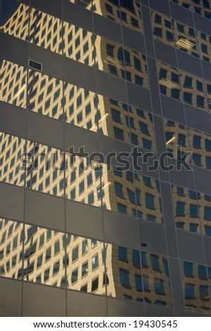Skyscraper windows reflecting another building - stock photo