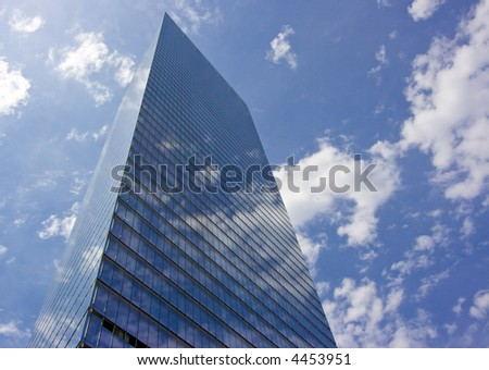 Skyscraper with clouds reflecting off of the windows - stock photo