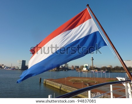 Skyscrapers along the river Meuse in Rotterdam in the Netherlands with the Dutch national flag - stock photo