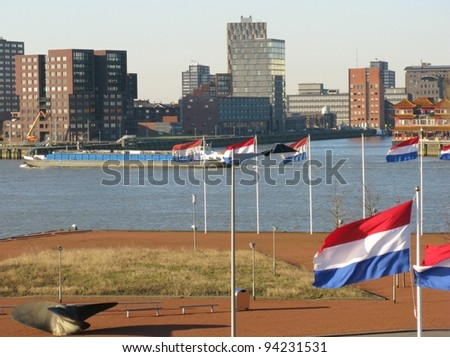 Skyscrapers along the river Meuse in Rotterdam in the Netherlands with the Dutch national flag in front - stock photo
