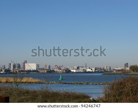Skyscrapers along the river meusse in Rotterdam seen from the nature island Brienenoord in the Netherlands - stock photo