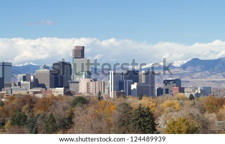 Skyscrapers in Denver, Colorado, with backdrop of the snowy Rocky Mountains and storm clouds.