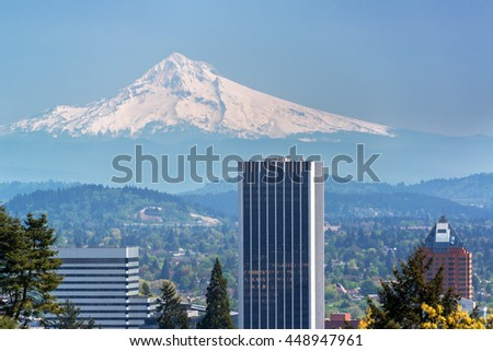 Skyscrapers in downtown Portland, Oregon with Mount Hood rising above them - stock photo