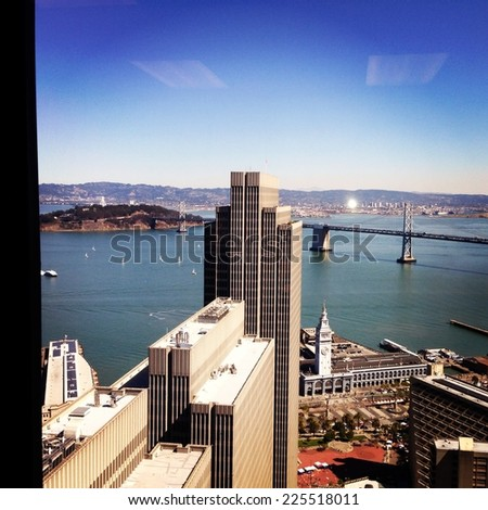 Skyscrapers overlooking a suspension bridge across the water. - stock photo