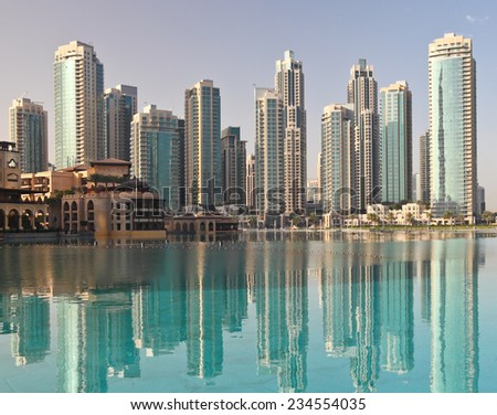Skyscrapers reflection in water at sunrise.  - stock photo