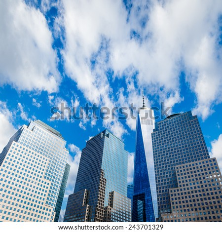 Skyscrapers rising up to blue sky with white clouds - stock photo