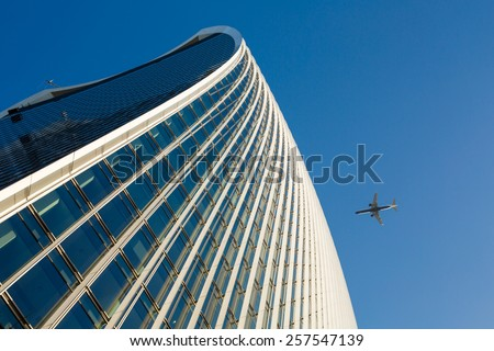 Skyscrapper and airplane flying over - stock photo