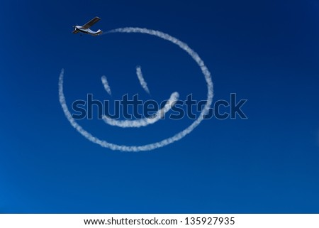 Skywriter airplane paints a happy smiley in the blue sky - stock photo