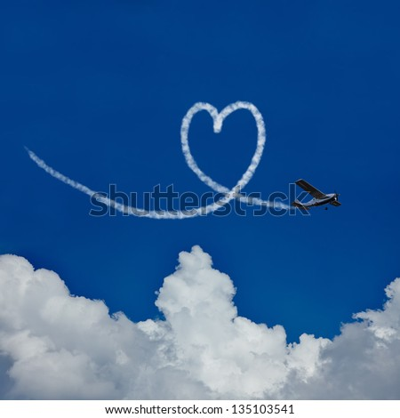 Skywriter paints a heart in the blue sky as symbol for love - stock photo