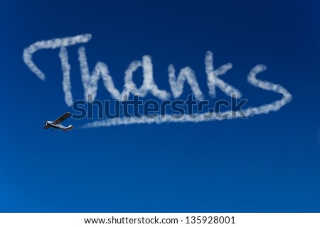 Skywriter writing the word Thanks in the blue sky - stock photo