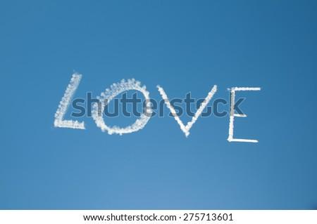 Skywriting Love on a blue sky with sun nearby - stock photo