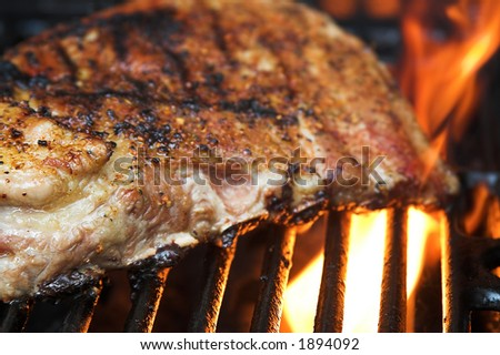 slab of ribs on grill with flames - stock photo