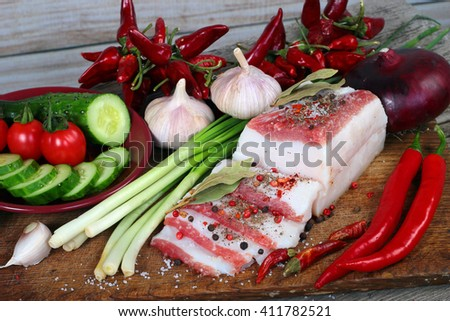 Slabs of salo, or salted pork fatback with spices. Traditional Slavic food with vegetables on wooden cutting board - stock photo