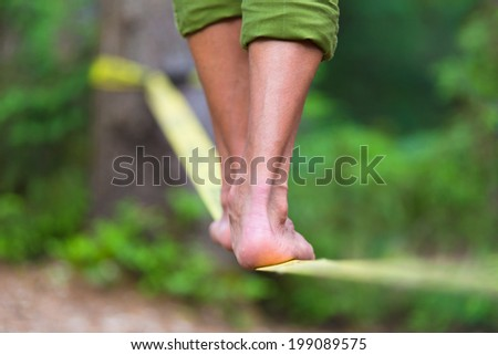 Slacklining is a practice in balance that typically uses nylon or polyester webbing tensioned between two anchor points. - stock photo