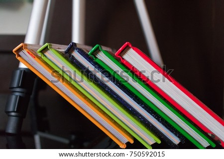 Slanting colorful books supported using tripod stand
