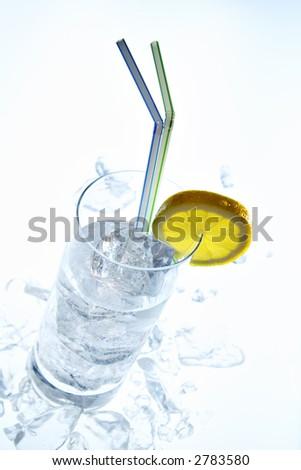 slanting longdrink glass with straws, ice cube, crushed ice, lemon slice - stock photo