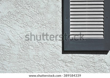 Slate blue shutters on stucco exterior wall - stock photo