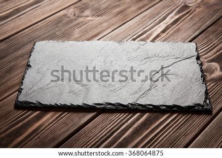 Slate board on wood - stock photo