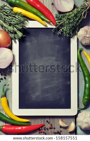 Slate board with fresh vegetables, spice and herbs on wooden background. Top view. - stock photo