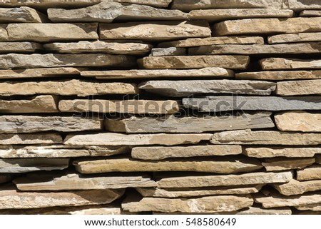slate flagstone wall of large irregular pieces of stone ruins brown background detail