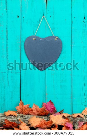 Slate heart hanging on rustic teal blue wood background by log covered in fall leaves border - stock photo