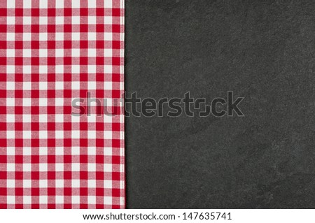 Slate plate with a red checkered tablecloth - stock photo