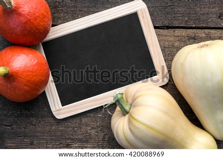 Slate with copyspace, Hokkaido and butternut pumpkins on wooden table - stock photo