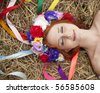 Slav girl with wreath lying at field - stock photo
