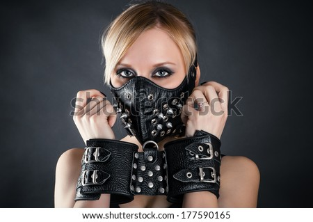 slave woman in handcuffs and a mask with spikes - stock photo