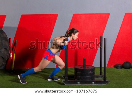 sled push woman pushing weights workout exercise at gym - stock photo