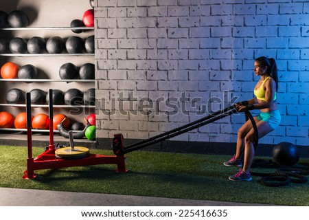 sled rope pull woman pulling weights workout exercise - stock photo