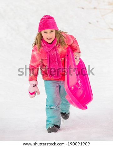Sledding Girl Walking Up Hill - determined girl walking up hill with pink snow sled.