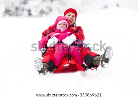 sledding mother and her little daughter - stock photo