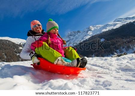 Sledding, winter fun, snow, family sledding at winter time - stock photo