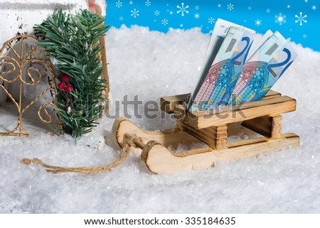 Sledge on snow with money gift, blue sky with snowflakes - stock photo