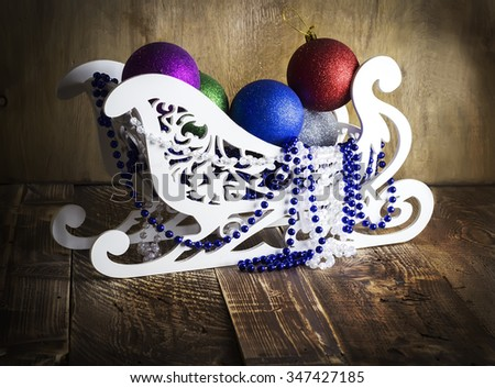 Sledge with big New Year's Christmas tree decorations on wooden texture - stock photo