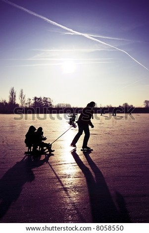 Sledging and ice skating on a cold winter day with purple sunset in the countryside from the Netherlands - stock photo