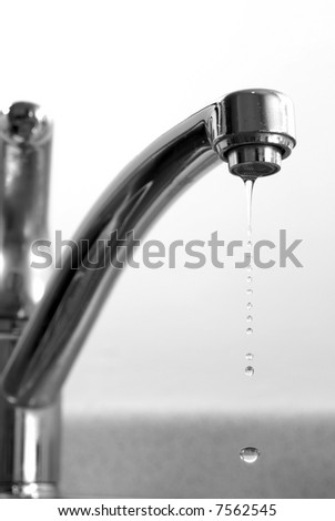 sleek black and white image of dripping long necked faucet with water drops stopped in motion