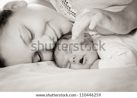 Sleep baby with mom, closeup faces - stock photo