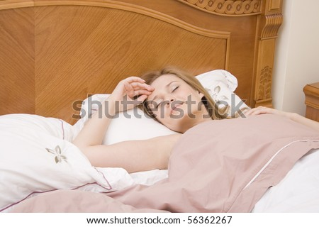 Sleeping and smiling woman in the bed at the morning