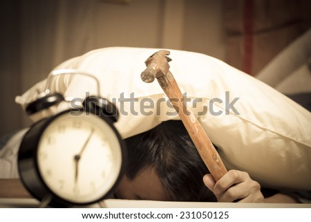 sleeping asian young male disturbed by alarm clock early morning on bed & holding hammer in hand - stock photo