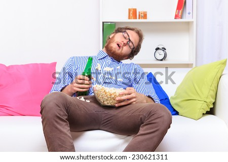 Sleeping at a party with popcorn and beer - studio shoot  - stock photo