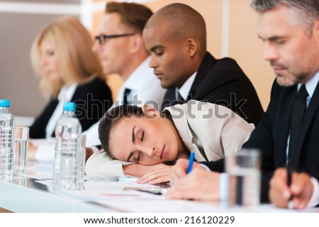 Sleeping at the conference. Tired businesswoman sleeping while sitting at the table with her colleagues  - stock photo